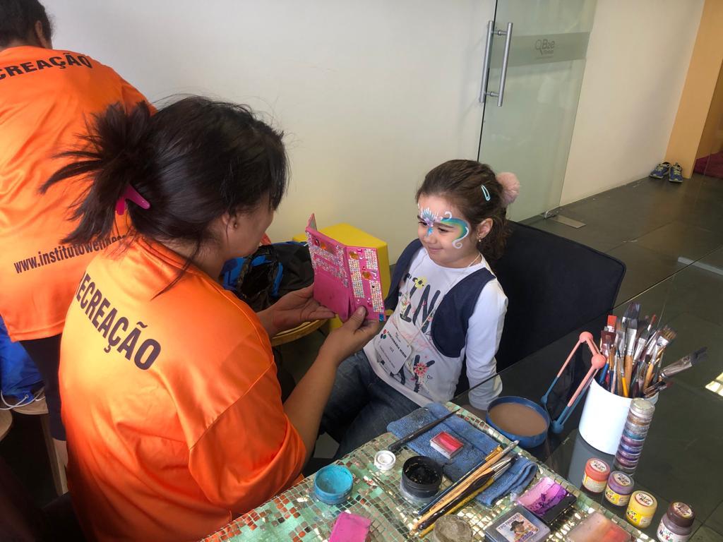 Recreadora e criança fazendo pintura facial